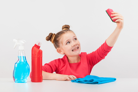 isolated on white, smiling red-haired girl in rose sweater holding a pink sponge and looking at it, a sky-blue spray, red detergent and a blue rag are on the white table. copyspace.