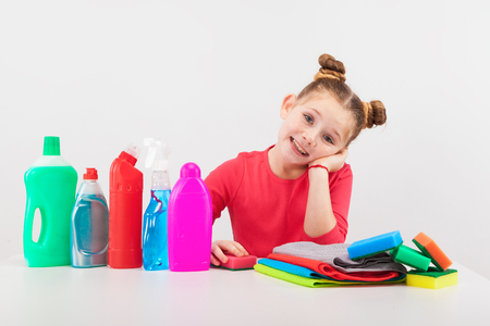 isolated on white, smiling red-haired girl in rose sweater propping up her cheek. multicolored detergents, rags and sponges are on the white table. copyspace.