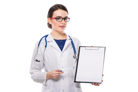 Portrait of young attractive female doctor in white coat standing in office smiling looking in camera and showing on clipboard confident friendly experienced skilful positive cheerful successful brunette caucasian beautiful pretty gp druggist pharmacist isolated.