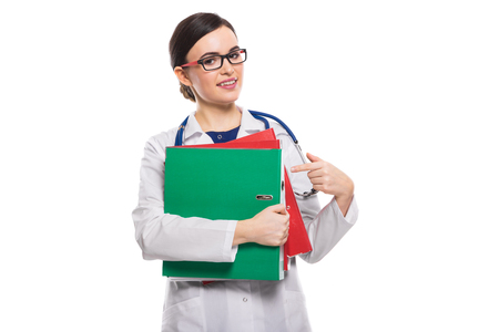 Portrait of young attractive female doctor in white coat standing in office smiling looking in camera showing ok and holding clipboards confident experienced friendly happy skilful positive cheerful successful brunette caucasian beautiful pretty gp manage success. Stock Photo