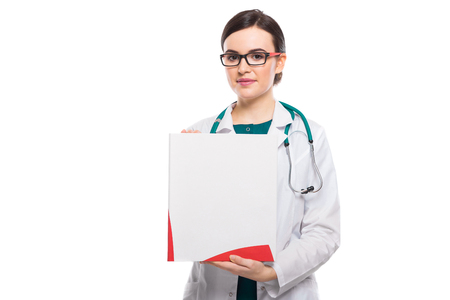 Portrait of young attractive female doctor in white coat standing in office smiling looking in camera and showing clipboard confident attentive experienced friendly skilful positive cheerful successful brunette caucasian beautiful pretty gp druggist dentist pediatrician.