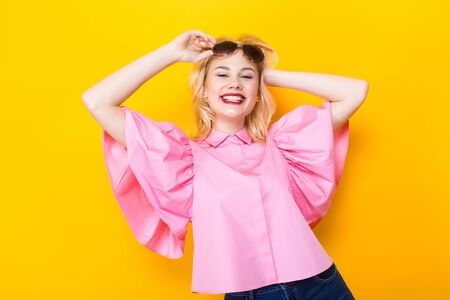 Portrait of cheerful laughing blonde woman with red lips in pink shirt and jeans shorts with sunglasses on orange background with copyspace touching her hair. Fashion advertisement concept.