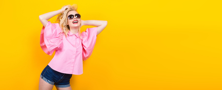 Portrait of cheerful blonde woman with red lips in pink shirt and jeans shorts with sunglasses posing on orange background with copyspace touching her hair. Fashion advertisement concept horizontal.