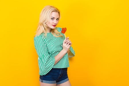 Portrait of attractive woman in striped shirt and jeans shorts with red lips isolated on orange background with copyspace holding two heart-shaped candies on sticks. Saint Valentines Day concept. Stock Photo