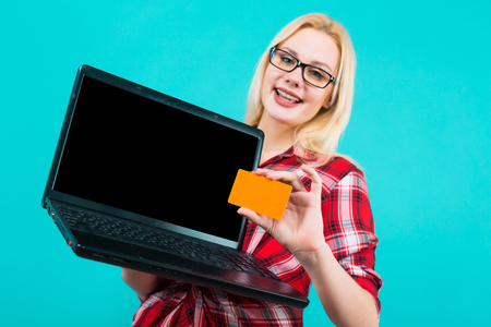 Portrait of attractive smiling blonde woman with glasses in red checkered shirt isolated on blue background holding laptop with blank business or credit card advertising loan concept. Stock Photo