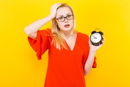 Portrait of attractive surprised blonde woman in glasses and red dress isolated on yellow background with copyspace holding alarm clock and touching her hair being late concept. Stock Photo