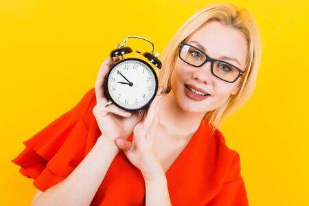 Portrait of attractive sexy blonde woman in glasses and red dress isolated on yellow background holding alarm clock being late concept.