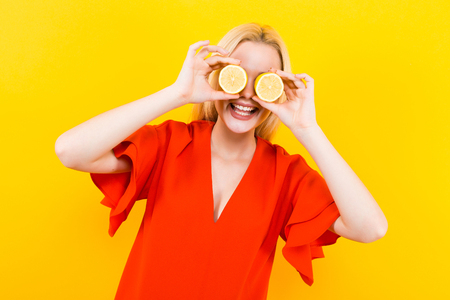 Portrait of attractive smiling woman in red dress isolated on yellow background holding two halfs of lemon citrus fruit in hands covering her eyes healthy diet nutrition happiness fun concept.