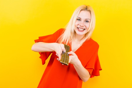 Portrait of attractive cheerful blonde woman in red dress isolated on yellow background holding TV remote and changing channels.