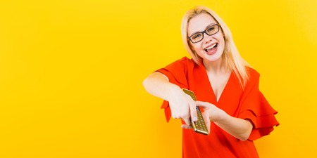 Portrait of attractive cheerful blonde woman in red dress and glasses isolated on yellow background holding TV remote and changing channels.