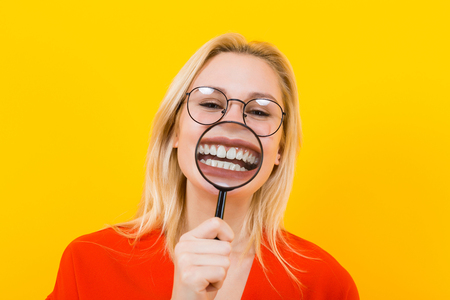 Portrait of attractive blonde woman in red dress and eyeglasses isolated on yellow background showing her teeth through magnifying glass. Фото со стока