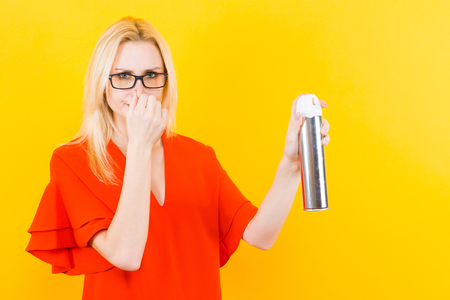 Portrait of attractive blonde woman in red dress and glasses isolated on yellow background holding air freshener aerosol and pinching her nose with fingers bad smell concept.