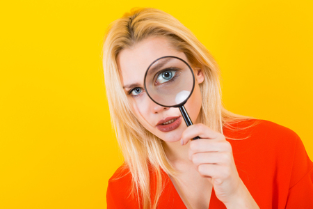 Portrait of attractive blonde woman in red dress isolated on yellow background looking through magnifying glass.