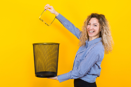 Portrait of curly-haired woman in striped shirt isolated on orange background throwing glasses she doesnt need any more into trash bin surgical correction of eyesight concept.