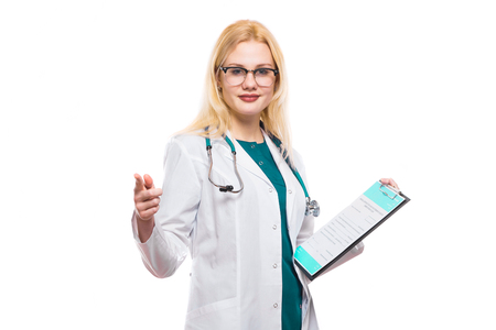 Female doctor in white coat and glasses wear stethoscope and hold clip pad with medical record application form pointing with her finger at camera isolated on white background with copyspace. Stock Photo