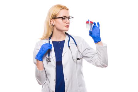 El retrato de la doctora en la bata blanca lleva el estetoscopio y los vidrios en guantes de látex miran el tarro para el análisis de orina aislado en el fondo blanco con el copyspace. Foto de archivo
