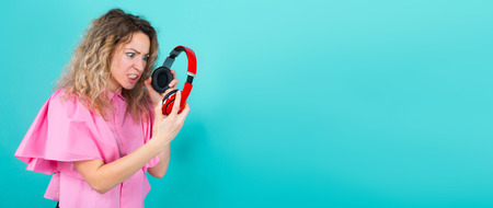 Portrait of attractive dissatisfied curly-haired woman in pink shirt isolated on blue background holding headphones frustrated depressed anger concept horizontal. Stock Photo