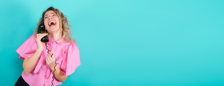 Portrait of attractive laughing curly-haired woman in pink blouse isolated on blue background talking on vintage phone and holding wire good news concept.