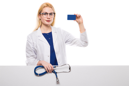 Portrait of female doctor in white coat and glasses holding stethoscope and showing her business card isolated on white background with copyspace insurance private clinic concept. Stock Photo