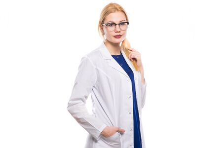 Portrait of female doctor in white coat and glasses touching her blonde hair and holding one hand in pocket isolated on white background with copyspace head physician concept.