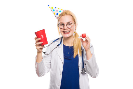 Funny female doctor glasses with stethoscope wears birthday cap and holds party whistle and red plastic cup with drink on white background with copyspace corporate medical party concept.