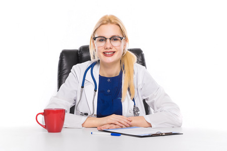 Female doctor or head physician in white coat and glasses with stethoscope sits in leather chair at table with coffee or tea fills in medical form on clipboard physician ready to examine patient. Stock Photo