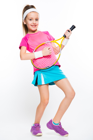 Adorable smiling little girl in sportswear holding tennis racket in her hands playing on tennis racket like on guitar on white background brunette caucasian beautiful funny attractive friendly isolated. Stock Photo