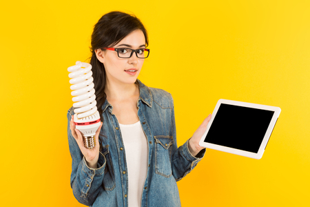 Portrait of attractive happy woman in denim shirt and eyeglasses isolated on yellow background holding light bulb working on laptop new ideas with innovation and creativity concept.