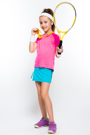 Adorable smiling little girl in sportswear holding tennis racket and medal in her hands on white background brunette caucasian beautiful attractive friendly lucky successful isolated gold silver bronze medal winner.