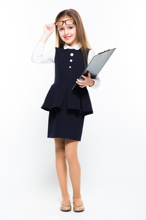 Adorable cute smiling little girl holding clipboard in her hands dressed as a businesswoman on white background brunette caucasian beautiful attractive happy successful confident isolated Standard-Bild
