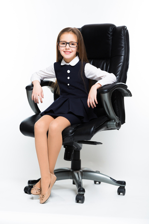 Adorable cute smiling little girl sitting in chair in office dressed as a businesswoman on white background brunette caucasian beautiful attractive happy successful confident isolated manage.