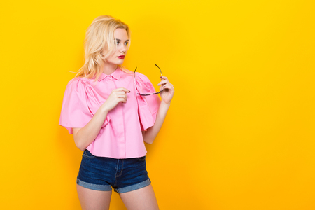 Portrait of attractive blonde woman with red lips in pink shirt and jeans shorts with sunglasses on orange background with copyspace. Fashion advertisement concept.