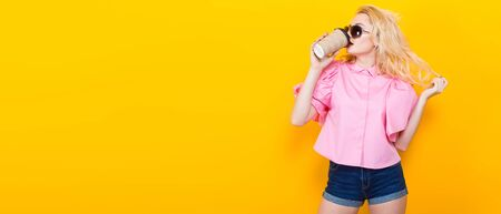 Blonde woman with red lips in pink shirt and jeans shorts with sunglasses drink takeaway coffee and pose on orange background with copyspace touch her hair. Fashion advertisement concept horizontal.