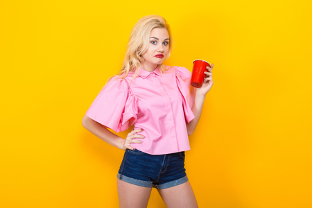 Portrait of attractive woman with red lips in pink shirt and jeans shorts with red plastic cup pose on orange background with copyspace show dissatisfaction on her face. Bad drink or not enough. 写真素材