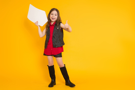Portrait of little cute girl in red shirt and high boots holding blank white arrow pointer with empty space for text directing towards herself isolated on orange background.
