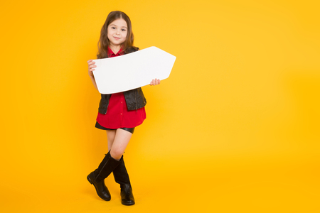 Portrait of little cute girl in red shirt and high boots holding blank white arrow pointer with empty space for text directing aside isolated on orange background.