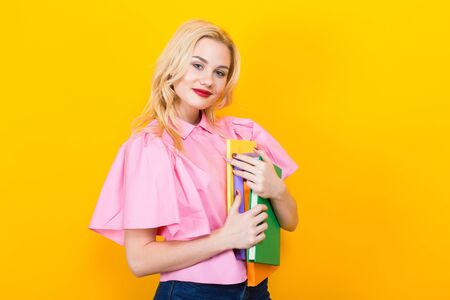 Portrait of attractive smiling blonde student girl with red lips in pink shirt and jeans with pile of books isolated on orange background with copyspace. Stock Photo