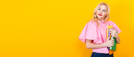 Portrait of attractive smiling blonde student girl with red lips in pink shirt and jeans with pile of books isolated on orange background with copyspace. Horizontal picture.