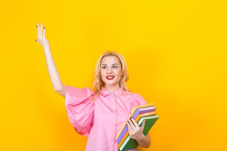 Portrait of smiling student girl with red lips in pink shirt and jeans with pile of books isolated on orange background with copyspace and holding her hand up, coming up with understanding concept.