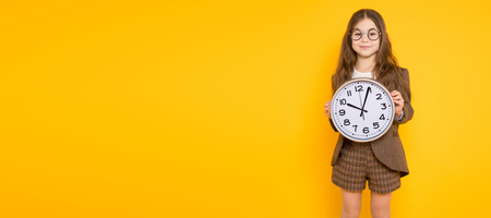 Portrait of long-haired little girl in eyeglasses wearing brown jacket, shorts and white knee-socks with watches isolated on orange background with copyspace school or sales time concept horizontal.