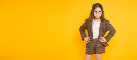 Portrait of adorable long-haired little girl in eyeglasses wearing brown jacket, shorts and white knee-socks with hands on waist isolated on orange background with copyspace kids fashion concept. Stock Photo
