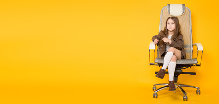 Portrait of long-haired little girl in eyeglasses sits in armchair wearing brown jacket, shorts and white knee-socks isolated on orange background with copyspace kids fashion concept horizontal.