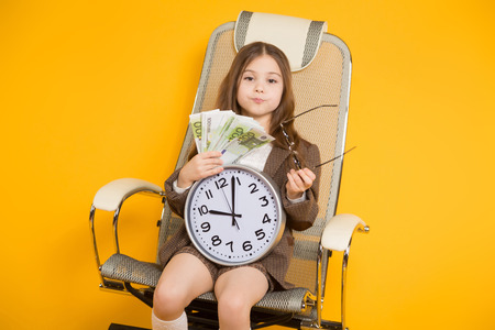 Long-haired little girl in eyeglasses sits in chair wearing brown jacket, shorts and white knee-socks with watches and fan of euro bills isolated on orange background with copyspace time is money. Stock Photo