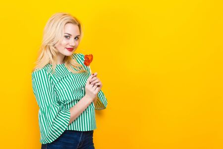 Portrait of attractive woman in striped shirt and jeans with red lips isolated on orange background with copyspace holding two heart-shaped candies on sticks. Saint Valentines Day concept.