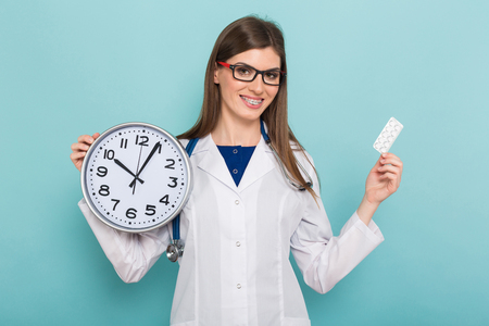 Portrait of smiling female doctor in white coat and glasses with braces on teeth holds clock and pills isolated on blue background with copyspace time to take medicine concept. Stock Photo