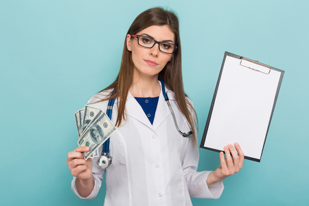 Female brunette doctor in white coat and glasses with stethoscope holds fan of dollar banknotes and blank paper clipped to pad isolated on blue background with copyspace bribe or paid services concept.
