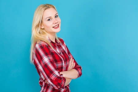 Portrait of attractive smiling blonde woman in plaid shirt standing with crossed arms isolated on blue background with copyspace.