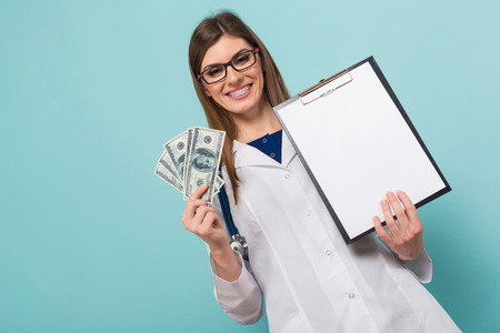 Female doctor in white coat and glasses with braces on teeth holds fan of dollar banknotes and blank paper clipped to pad isolated on blue background with copyspace bribe or paid services concept. Stock Photo