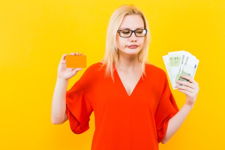 Portrait of disappointed woman in glasses and red dress isolated on yellow background hold blank credit card and fan of euro banknotes earn on the internet withdraw money loan mortgage concept.