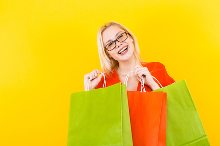 Portrait of attractive happy blonde woman in red dress and glasses isolated on yellow background holding colourful shopping paper bags.